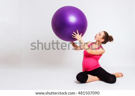 young pregnant woman meditating on a light background, practice yoga. Health Care and Pregnancy