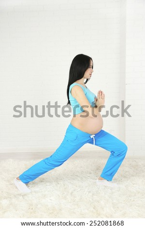 Young pregnant woman on light background. Yoga for pregnant women concept - stock photo