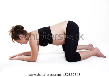 Young pregnant woman practises yoga asana - stock photo