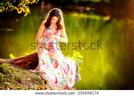 Young pregnant woman relaxing in park outdoors, healthy pregnancy. Beautiful pregnant woman holding her tummy. Pregnant woman walking in park - stock photo