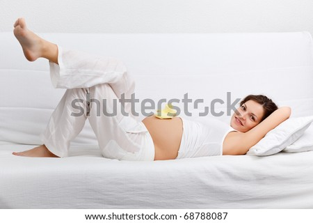 Young pregnant woman relaxing on sofa - stock photo