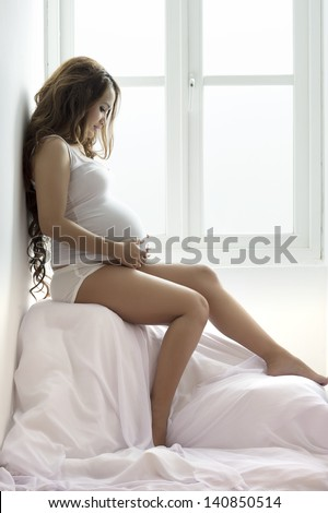 young pregnant woman sitting on the window