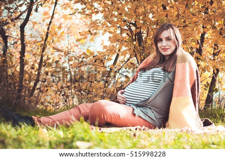 Young pregnant woman with a big belly on outdoors