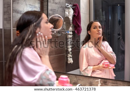 Young pregnant woman with cosmetic cream  in a bathroom. Concept body care.