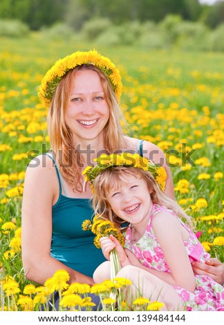 Young pregnant  woman with cute little girl enjoying a summer day outdoors - stock photo