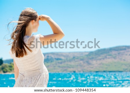 Young pregnant woman with her hair in summer dress standing by blue sea and looking into the distance - stock photo