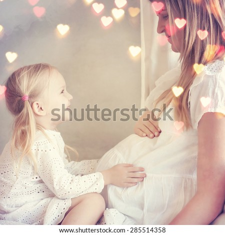 Young pregnant woman with her little daughter - stock photo