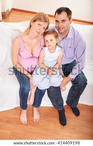 Young pregnant woman, with husband and little daughter