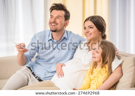 Young pregnant woman, with husband and little daughter are watching TV together. - stock photo