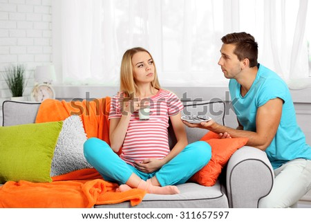 Young pregnant woman with husband on sofa in room