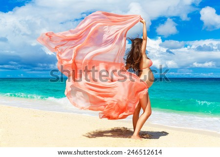 Young pregnant woman with pink cloth fluttering in the wind on a tropical beach. outdoors, healthy pregnancy. Happy pregnant woman on nature. New life concept. - stock photo
