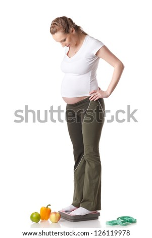 Young  pregnant woman with scales and fruit on a white background.  Concept of healthy lifestyle. - stock photo