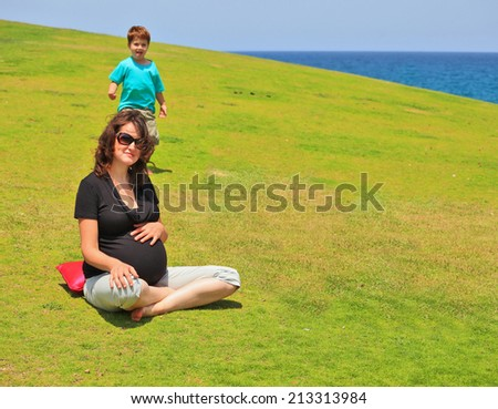 Young pregnant woman with sunglasses posing for a photograph on the grass lawn. Her young son laughing runs to her - stock photo