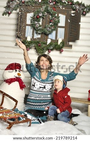 Young pregnant woman with the child about a snowman - stock photo