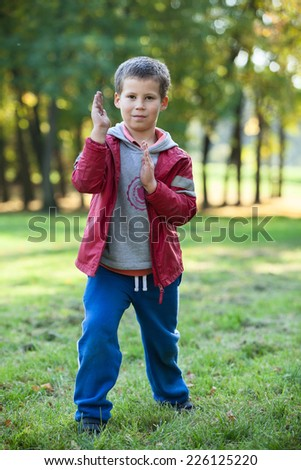 Young preschool boy showing karate techniques in autumn park - stock photo