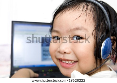 Young preschool girl, listening to music or a video on a laptop computer. - stock photo