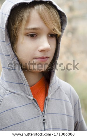young preteen boy outside dressed in a hoodie - stock photo