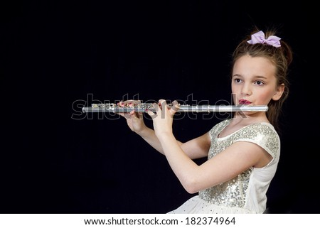 Young preteen girl playing her flute against black background - stock photo