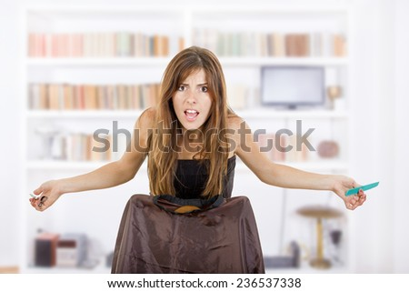 Young pretty angry woman hairdresser with comb and scissors waiting impatiently for customer at home or hair salon. Concept of insufficient work in profession while seeking job - stock photo
