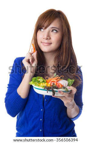 Young pretty asian  girl eating fresh vegetable salad, isolated on white background