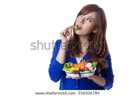 Young pretty asian  girl eating fresh vegetable salad, isolated on white background - stock photo