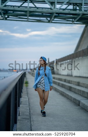 Young pretty Asian girl wear blue jean shirt and cap posing on Akashi Kaikyo Bridge sunset   at Kobe , Japan.