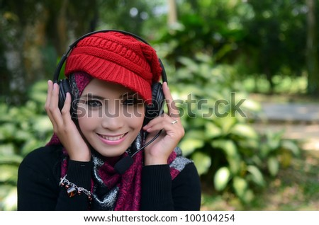 young pretty Asian muslim college girl  listen to music. - stock photo