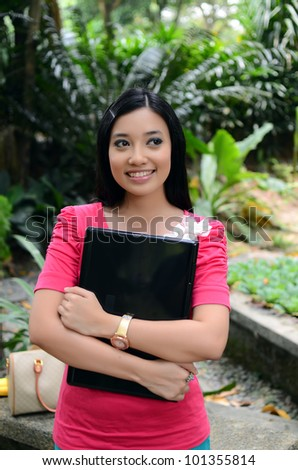 young pretty Asian muslim college girl with labtop and smile