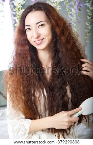 Young pretty asian woman combing her long hair in a bedroom in a morning