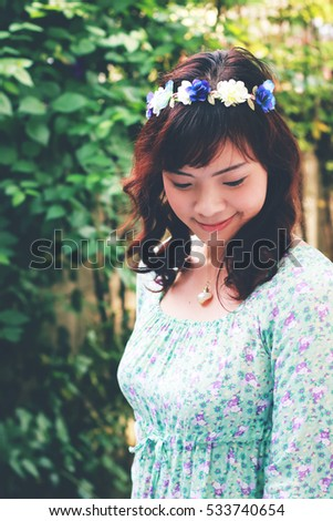 Young pretty Asian woman with flower headband in vintage tone.