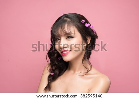 young pretty asian woman with flowers on hair close up on pink background - stock photo