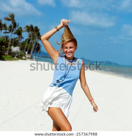 Young pretty beautiful smiling happy tanned woman posing on the beach in summer showing her tongue and feels happy  - stock photo