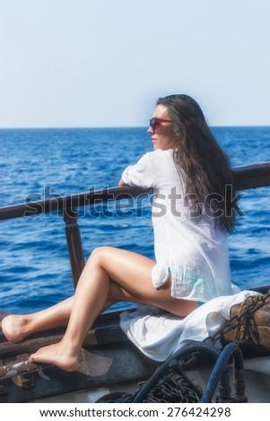 Young pretty - beautiful woman on the deck yacht enjoys cruising - stock photo