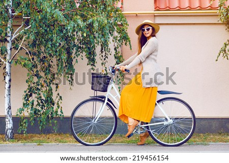 Young pretty beautiful woman riding her white retro hipster bike,wearing stylish vintage clothes sunglasses and straw hat, fashion fall autumn portrait of elegant lady having fun outdoor. - stock photo