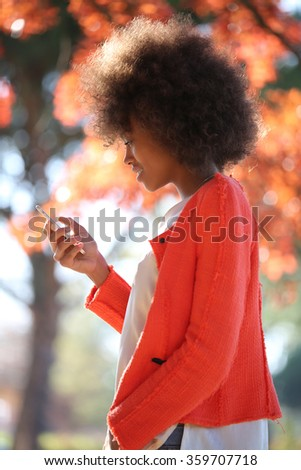 Young pretty black woman walking in park during fall and using cellphone - stock photo