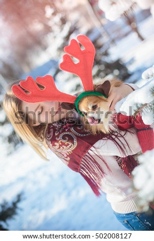 Young pretty blond girl in a winter snow-covered park holds a Pomeranian with red reindeer horns