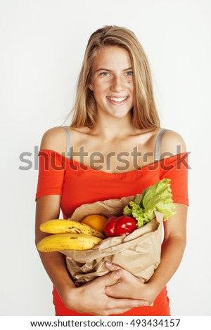young pretty blond woman at shopping with food in paper bag isolated on white smiling bright, lifestyle people concept