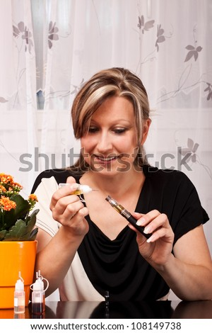 young pretty blond woman filled with liquid flavor their electric cigarette - stock photo