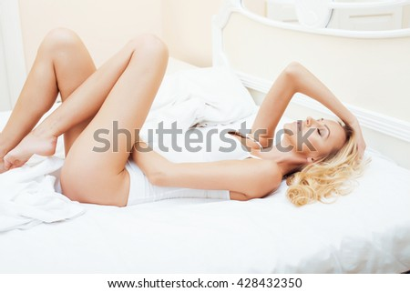 young pretty blond woman in bed covered white sheets smiling cheerful sexy look close up, happy morning concept - stock photo