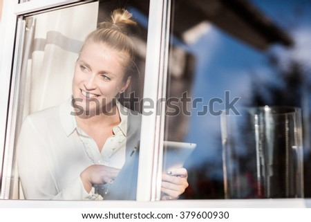 Young pretty blond woman sitting at the window with her tablet and relaxing in the sun - stock photo