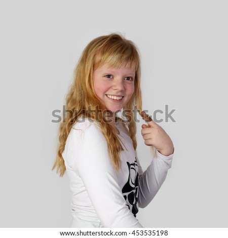 Young pretty blonde girl smiles and pulls golden hair on finger on gray background - charming beauty of youth - stock photo