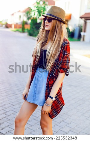 Young pretty blonde hipster girl posing on the street, wearing plaid shirt, mini denim skirt, hat and sunglasses, urban style.