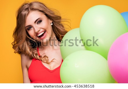 Young pretty blonde woman posing with colorful balloons. Yellow background. Studio shot. Happiness content. Toothy smile. - stock photo