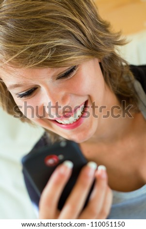 young pretty blonde woman with mobile at home
