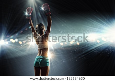 Young pretty boxer woman standing in light flashes - stock photo