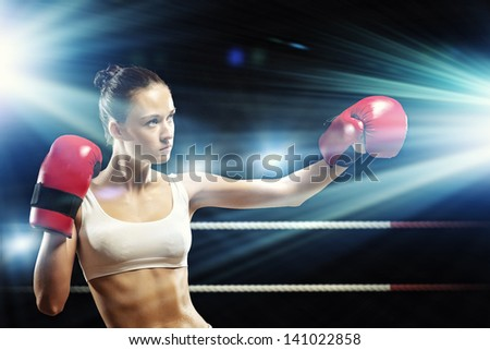 Young pretty boxer woman standing on ring - stock photo