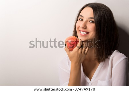 young pretty brunette girl eatingapple isolated on white - stock photo