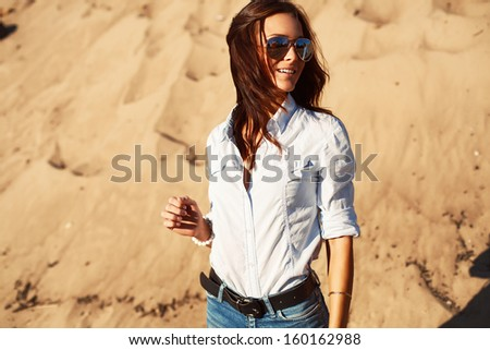 Young pretty brunette girl posing outdoor in summer on the beach - stock photo