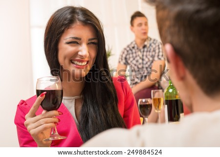 Young pretty brunette girl with a glass of wine in hand, with a smile looking at the guy who has his back turned to the camera. - stock photo