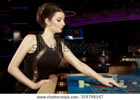 Young pretty brunette lady with roulette table in casino